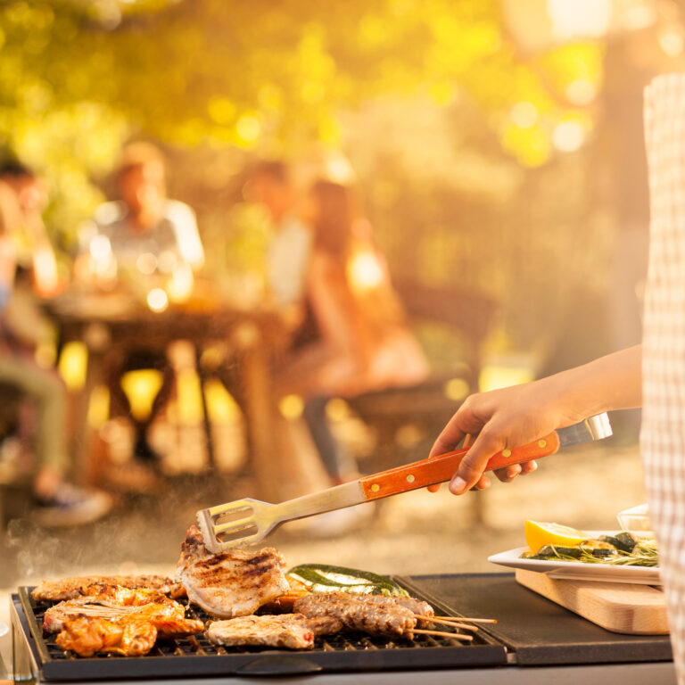 Rosting meat on barbecue for a family picnic in the back. Sun through the trees.